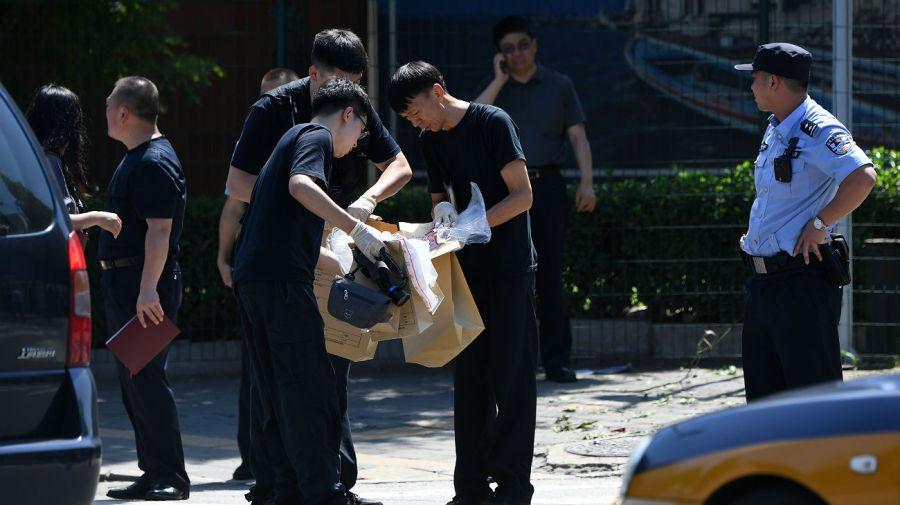 Oficiales chinos, trabajando en la investigación de la explosión en la embajada estadounidense en Pekín.