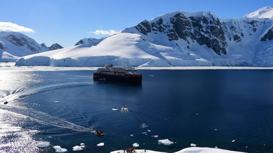 Cruise ship and tourists landing in antarctica stock