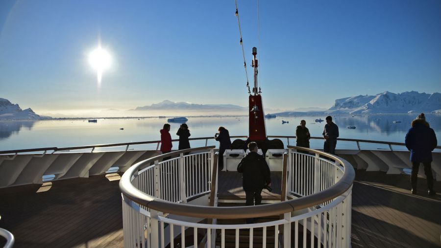 Tourists watch sunset on boat in Antarctica stock