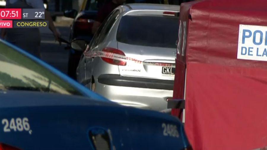 El Peugeot gris estacionado en Congreso. Su conductor huyó luego de cruzar en rojo y matar a un hombre que esperaba el colectivo.