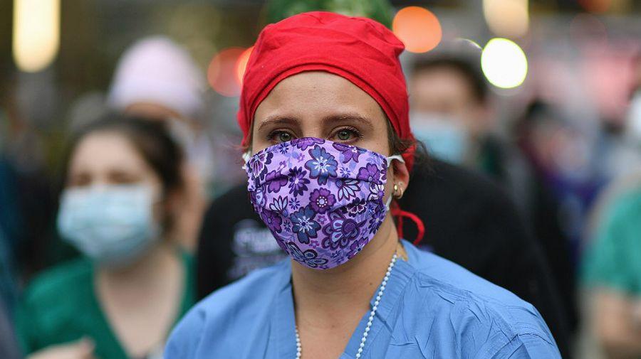 Una trabajadora de salud mira a la gente que aplaudía a los médicos y enfermeras frente a Langone Health Hospital, este jueves en Nueva York.