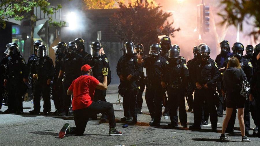 Un hombre se arrodilla ante un grupo de policías, en el medio de las protestas antiracismo en Oakland, California, este viernes 29 de mayo.