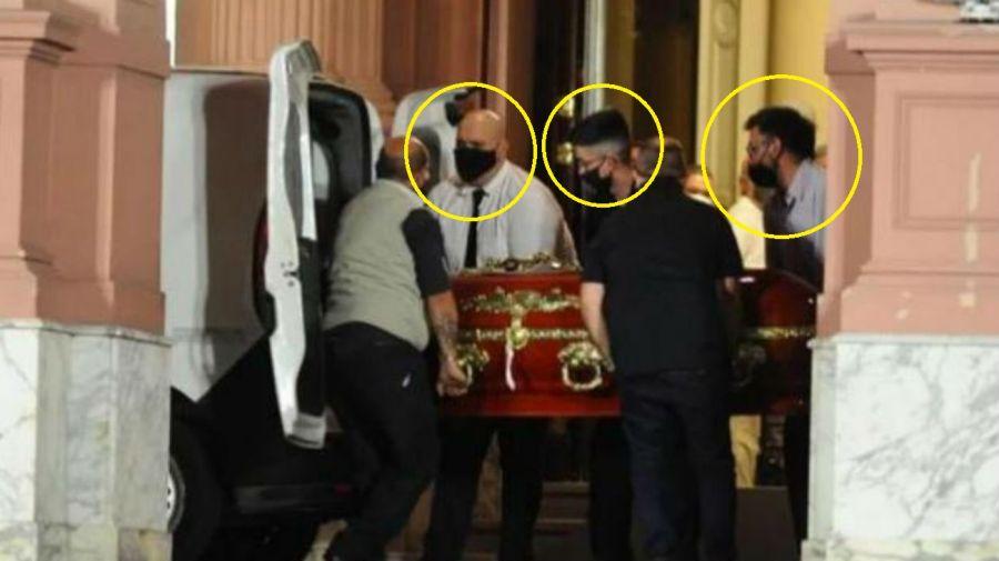 Empleados repudiados llevando el cajón de Diego Maradona