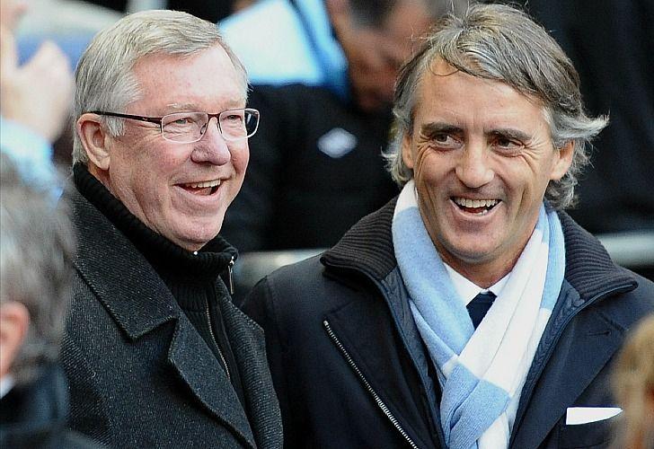 Los técnicos del Manchester United y el Manchester City, Alex Ferguson y Roberto Mancini, hablan antes del partido de este lunes. /AFP