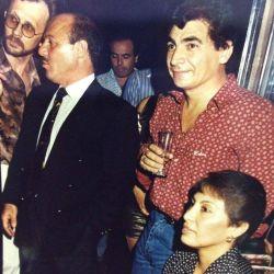 Martins de traje hablando con su primo proxeneta y Rubio con la copa en mano