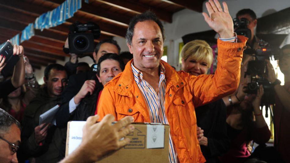 Scioli, de campera naranja, al emitir su voto.
