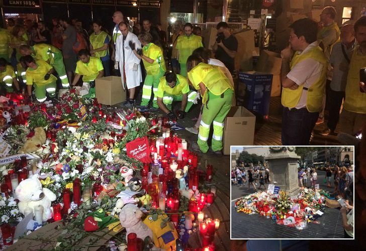 Ante la atenta mirada de Pisarello, los empleados municipales retiran las flores del espacio memorial.