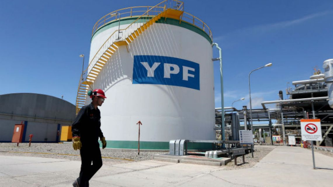 A worker walks past a YPF oil tank in Neuquén