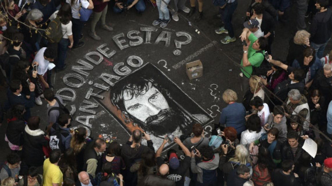 People surround a portrait painted on the street of Santiago Maldonado during a demonstration called by human rights associations.