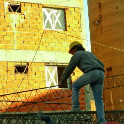A construction worker carries building materials on a building site in the capital.