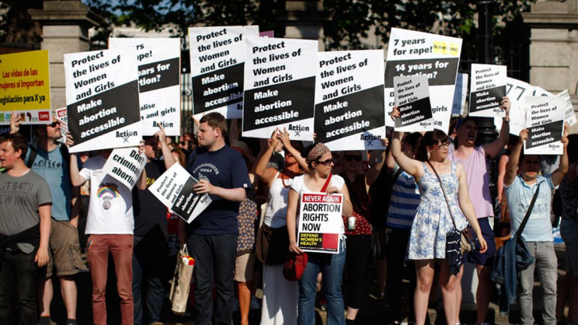 This file photo taken on July 10, 2013 shows Pro-Choice supporters hold placards in front of the gates of the Irish Parliament building in Dublin during a demonstration.