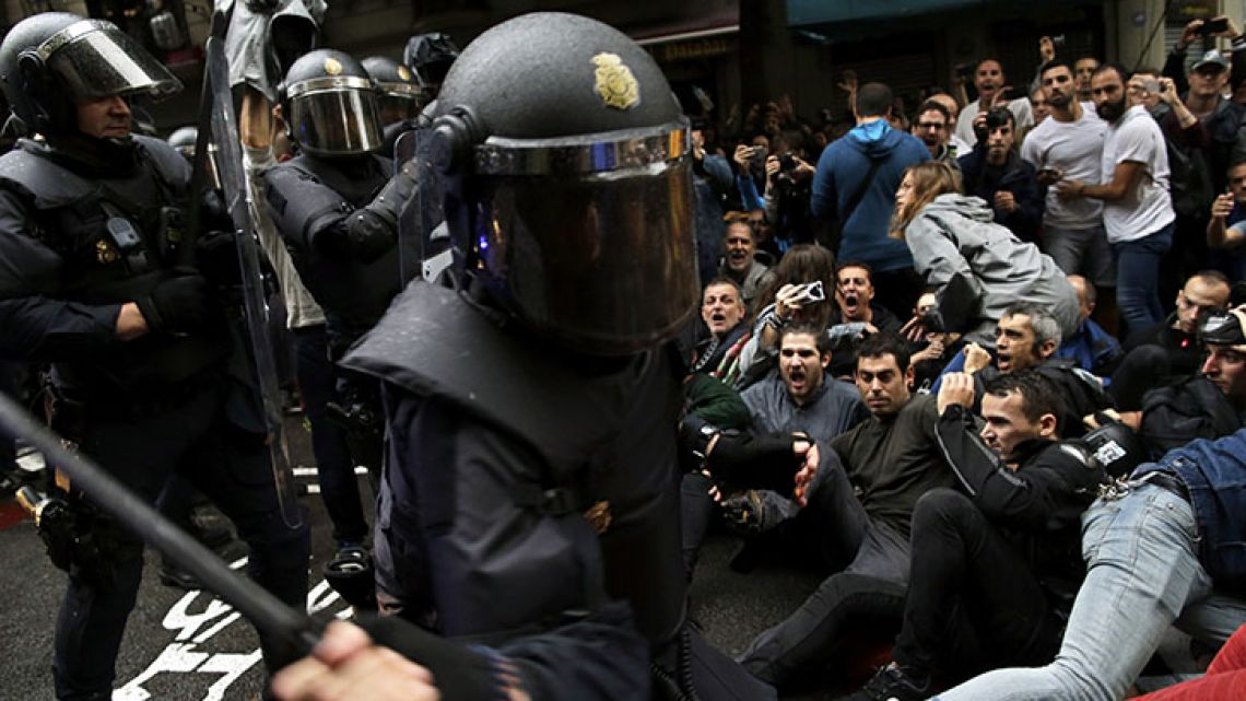 Spanish National Police attack pro-referendum supporters sitting down on a street in Barcelona on Sunday.