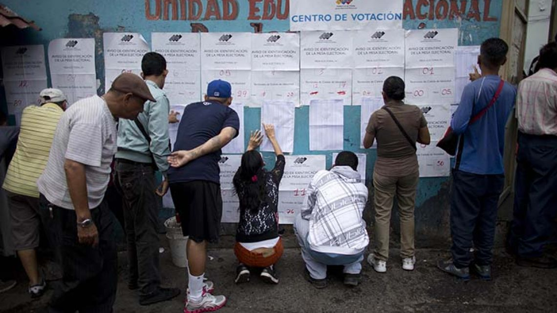 People look for their names on voter registration lists outside a polling station during regional elections in Caracas, Venezuela on Sunday.