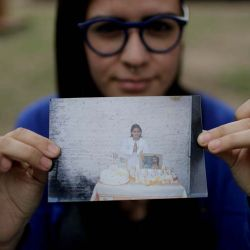 Karen Maydana, 22, shows a picture of herself as a child celebrating her first Holy Communion in Caseros, in the province of Buenos Aires, Argentina. Maydana says she was nine years old when the Reverend Carlos José fondled her at a church pew facing the altar on the day of her first confession ahead of her first Holy Communion.