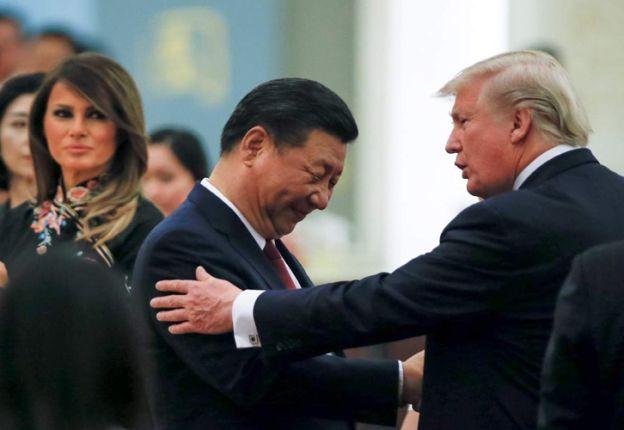 Trump saluda a Xi Jinping bajo la atenta mirada de su esposa Melania.