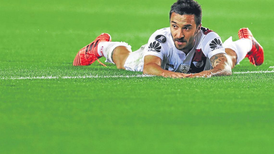 River Plate's Ignacio Scocco lies on the field during the team's Copa Libertadores semi-final defeat against Lanús on Tuesday.