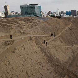 Tourists walk the trails of the pre-Columbian archeological site Pucllana, surrounded by modern high-rises in the Miraflores district of Lima, Peru. Peruvians have lived their entire lives alongside the huacas, an indigenous Quechua word meaning sacred place