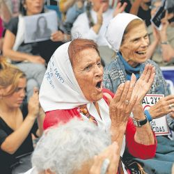 Mothers of Plaza de Mayo member Tati Almeida, front, celebrates as she listens to verdicts against former members of the Armed Forces, while watching the trial on a screen outside the court building in Buenos Aires.