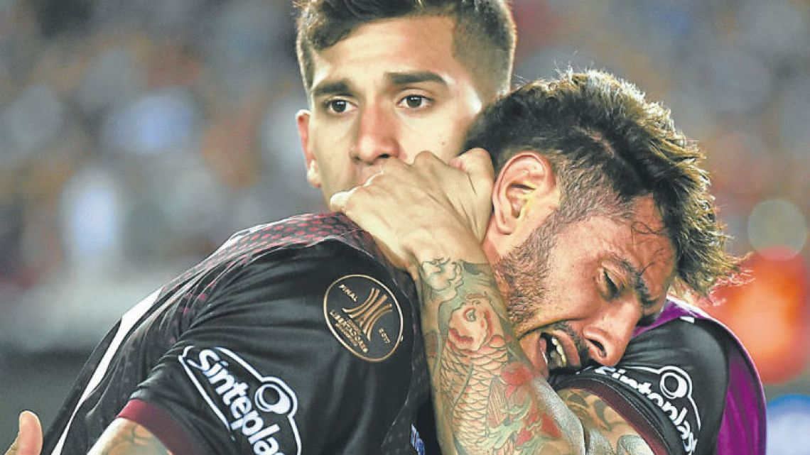 Lanús players console each other after their defeat in the Copa Libertadores final to Gremio.