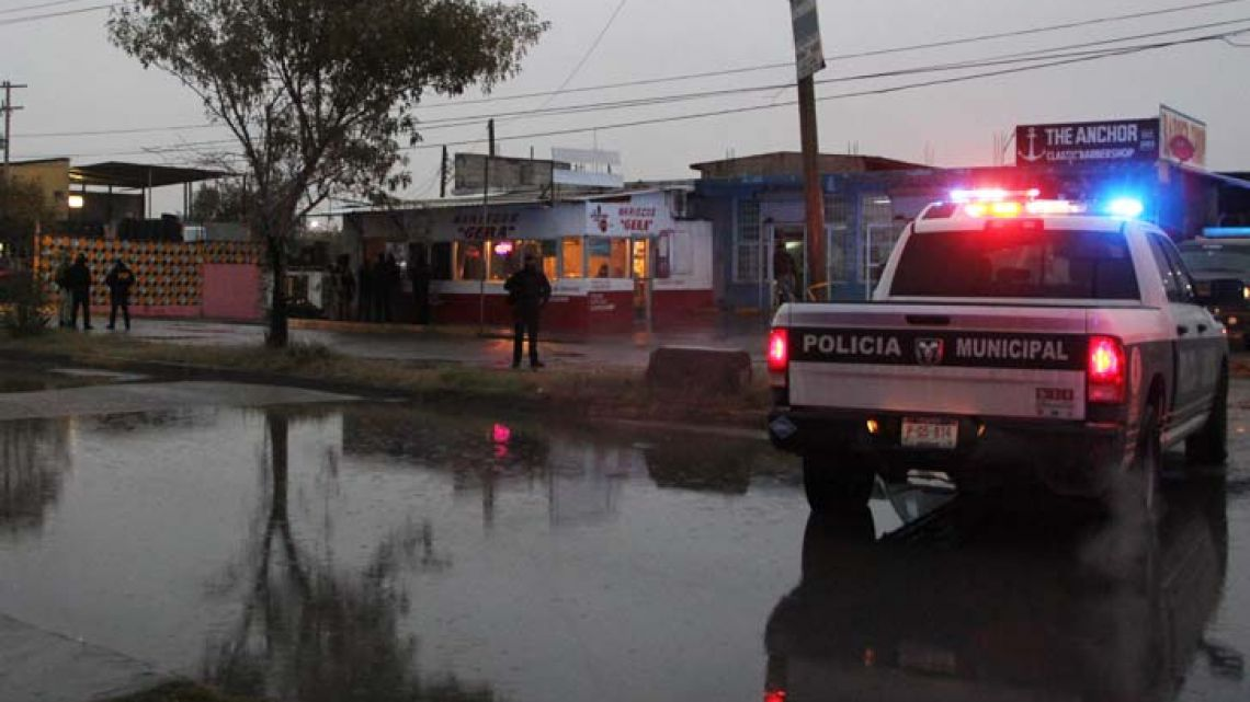 Members of police forces and investigators guard a crime scene where six people were machine-gunned by unknown men at a business in Ciudad Juárez, Chihuahua state on December 6, 2017.