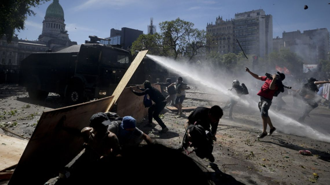 Protesters clash with police during a demonstration against a pension reform measure, outside Congress on Monday.