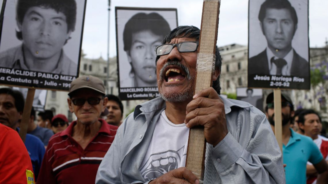 A protester demonstrates against the decision to pardon of former Peru president Alberto Fujimori, while fellow demonstrators hold up photographs of nine university students who were kidnapped, killed and disappeared in 1992 by the undercover military group Colina, in Lima on Christmas Day.