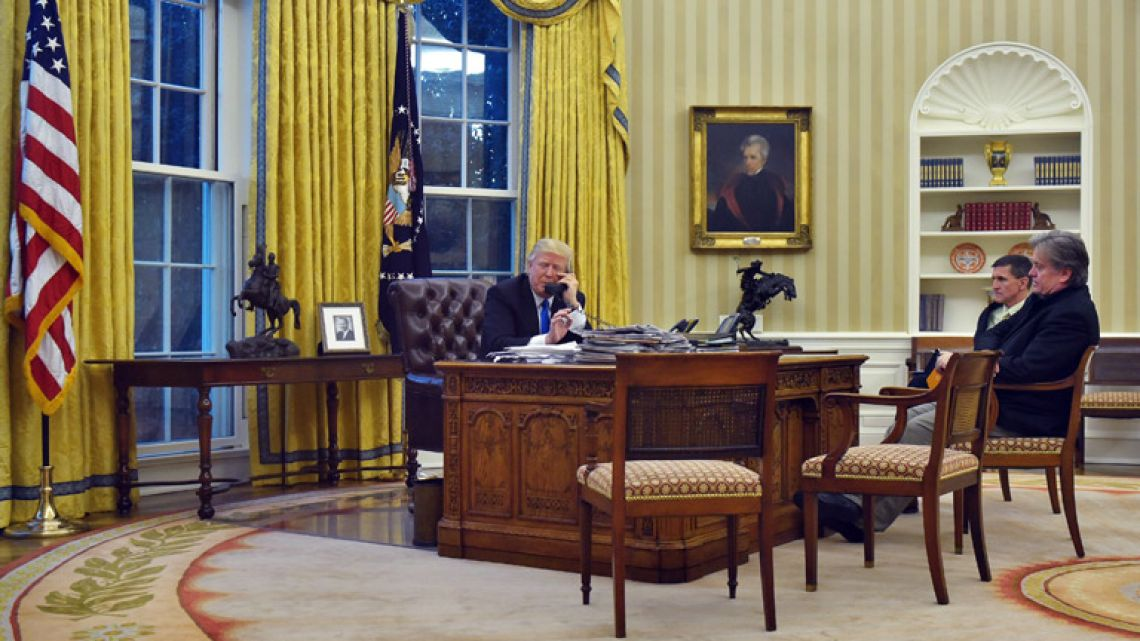 This file photo taken on January 28, 2017 shows US President Donald Trump speaking on the phone with Australia's Prime Minister Malcolm Turnbull, alongside former Chief Strategist Steve Bannon (right) and former National Security Advisor Michael Flynn, from the Oval Office of the White House in Washington.