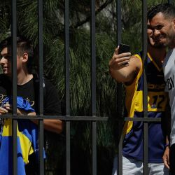 Fans take a photograph with Boca Juniors striker Carlos Tevez at training, after the Argentine forward's first session with his teammates following his return from China.