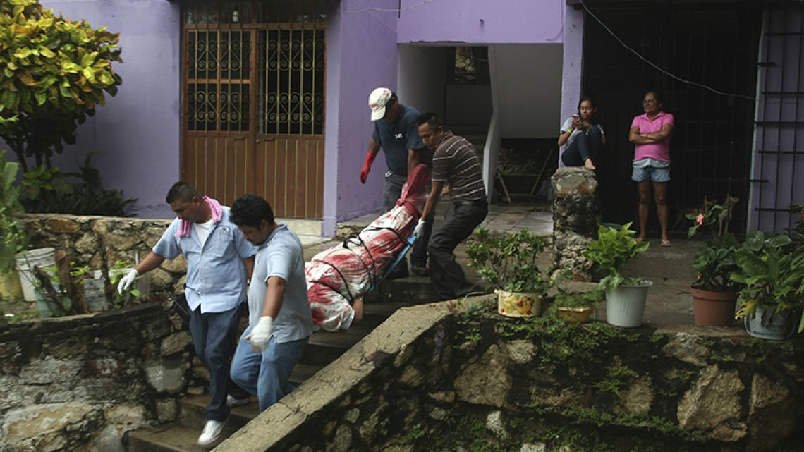 In this August 29, 2017 file photo, a body wrapped in a bloodstained sheet is removed from an apartment building where a woman and two men were executed, in the Alta Progreso neighbourhood of Acapulco, Mexico. Both men were bound with tape, and all three were shot in the head at an apartment outfitted as an office for a taxi service. Mexico's Interior Department posted on Sunday, January 21, 2018 that the country's homicide rate is the highest in decades.
