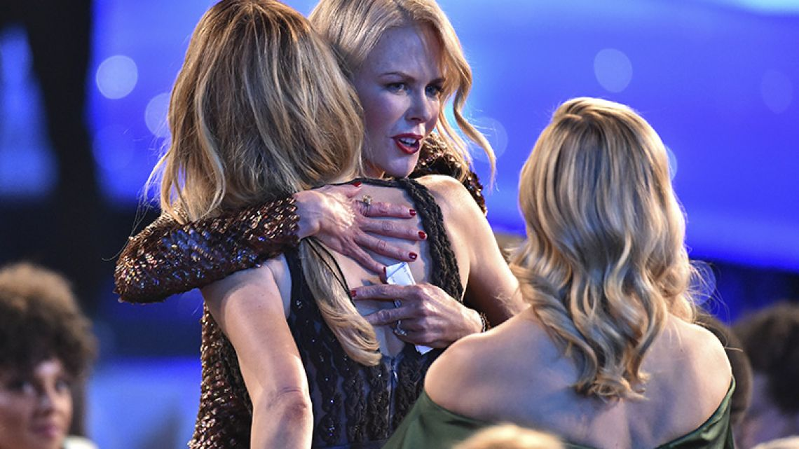 Laura Dern, left, and Reese Witherspoon, right, congratulate Nicole Kidman in the audience as she accepts the award for outstanding performance by a female actor in a television movie or limited series for