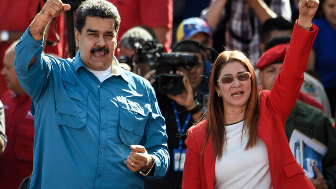 Venezuelan President Nicolás Maduro (left) and First Lady Cilia Flores (right) greet supporters during a rally in Caracas.