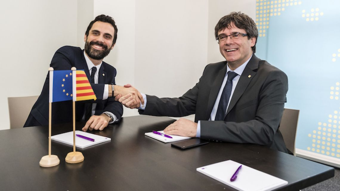 Ousted Catalan leader Carles Puigdemont, right, shakes hands with Catalonian Parliament President Roger Torrent last week in Brussels.