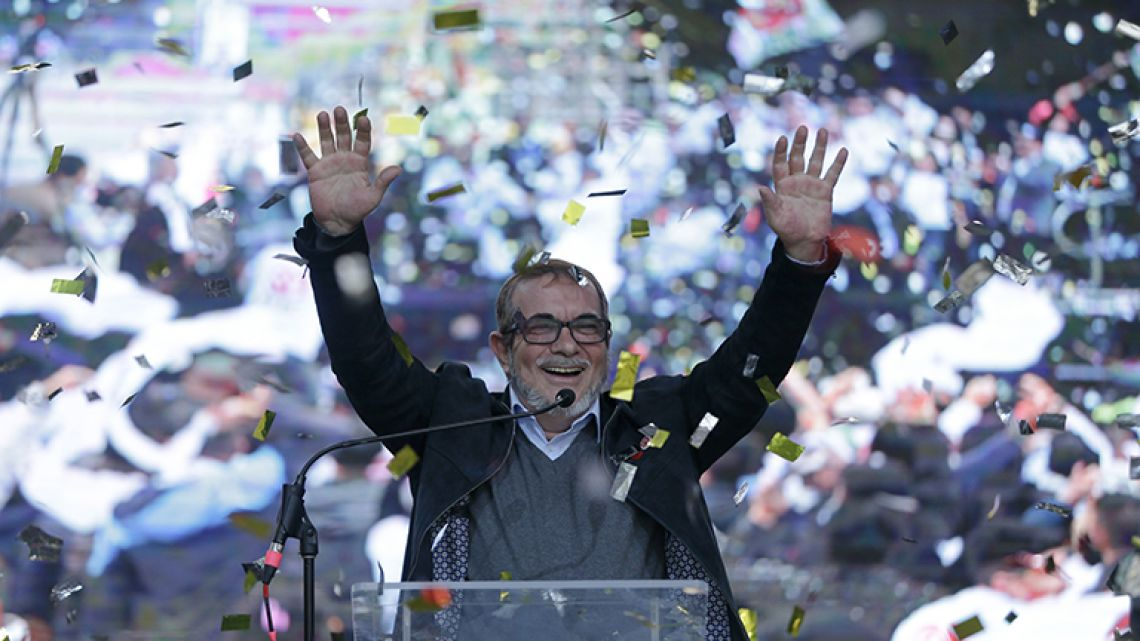 Rodrigo Londoño, known as Timochenko, salutes at an event to present candidates running for Congress for the political party formed by former guerrillas of the Revolutionary Armed Forces of Colombia, FARC, in Bogota, Colombia.