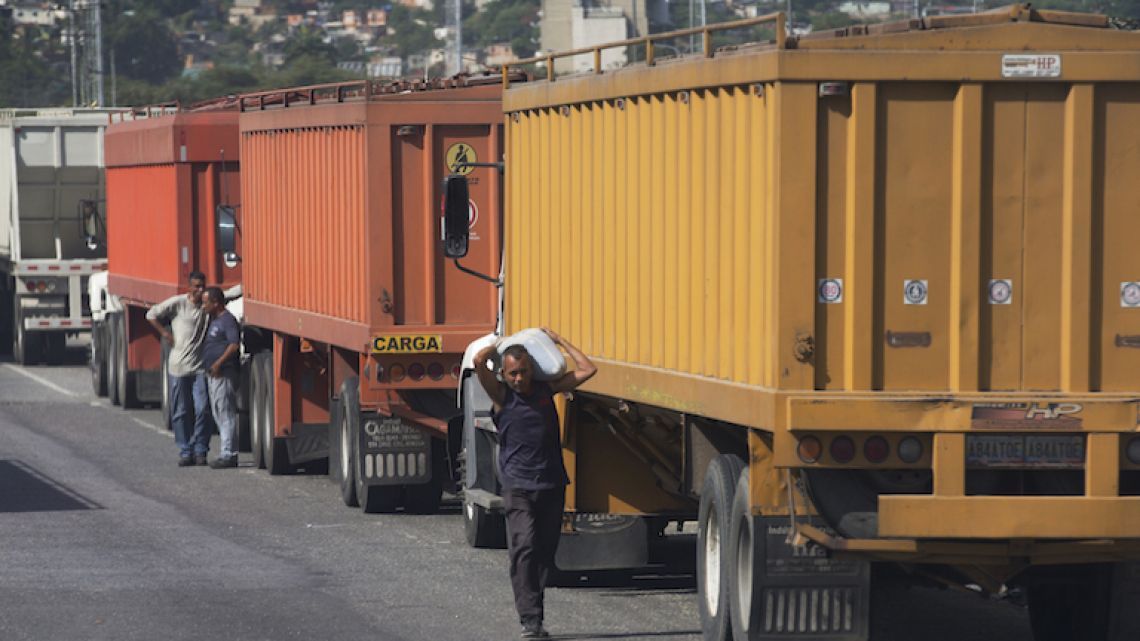 A man carries a sack of white corn he stole from grain-carrying trucks parked outside the port in Puerto Cabello, Venezuela.