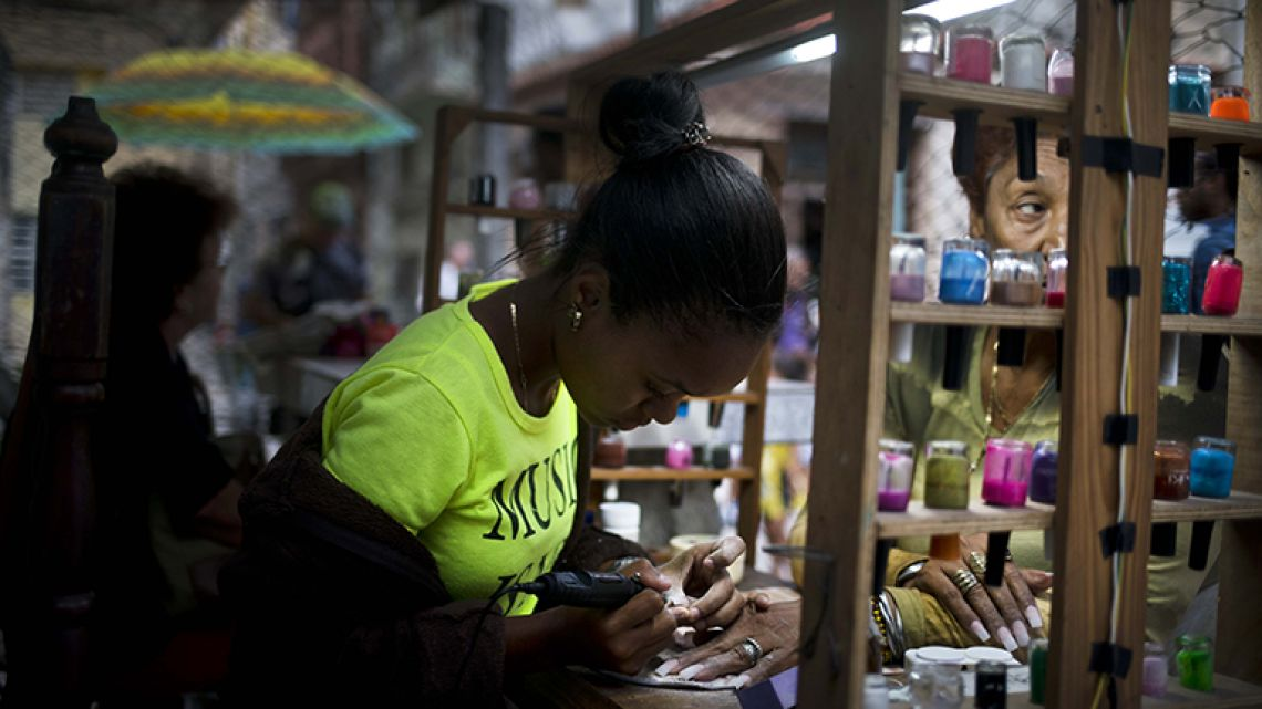A private manicurist, who is part of a cooperative, services a client in Havana, Cuba.