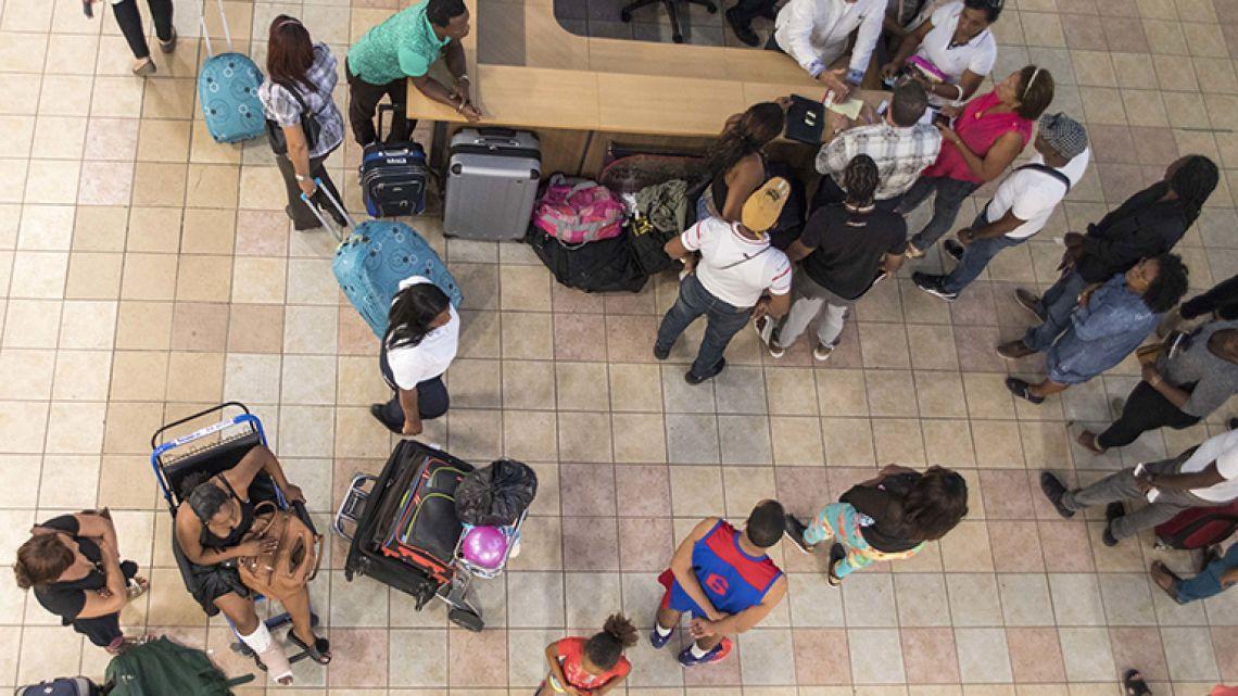 Stranded Pawa Dominicana passengers gather around the Civil Aviation Board information desk, at Las Americas International Airport in Santo Domingo, Dominican Republic.