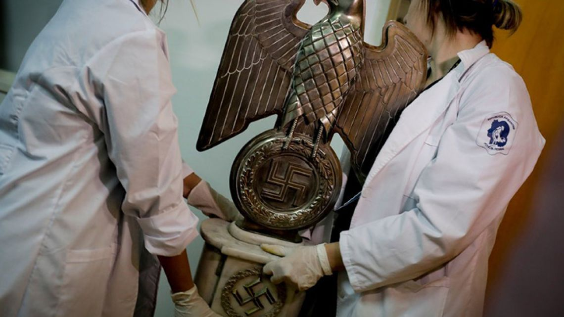 Argentine authorities study Nazi-era objects that were seized during a raid in June last year.