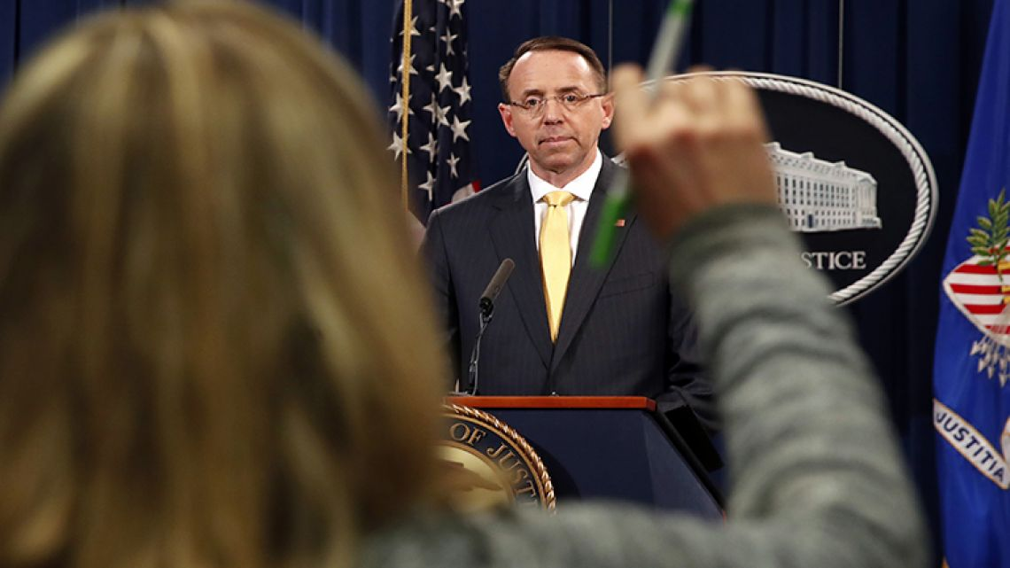 A reporter raises her hands to ask a question of Deputy Attorney General Rod Rosenstein, after he announced that the office of special counsel Robert Mueller says a grand jury has charged 13 Russian nationals and several Russian entities in Washington.