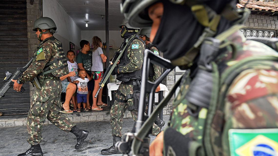 Army soldiers patrol the Vila Kennedy favela in Rio de Janeiro on February 23, 2018. More than 3,000 soldiers supported Rio de Janeiro police Friday in a sweep of three violence-plagued favelas in the west of the Brazilian city, officials said.