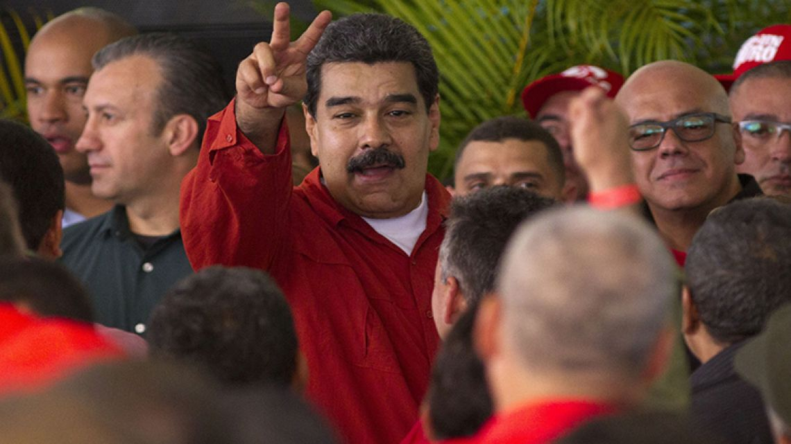 Venezuela's President Nicolas Maduro flashes a victory sign to supporters during a ceremony formalizing his candidacy as a candidate for the upcoming presidential election, at the CNE in Caracas, Venezuela, Tuesday, February 27, 2018.
