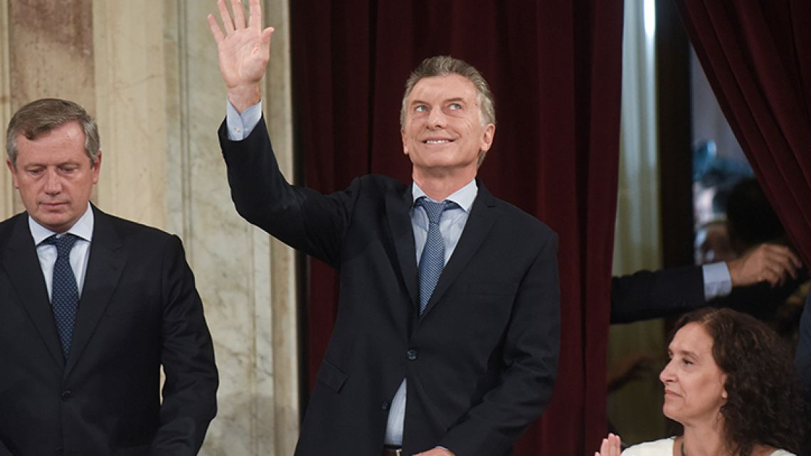Argentina's President Mauricio Macri waves as he arrives to open the 2018 session of Congress and give the annual State of the Nation address, flanked by Emilio Monzo, president of the Chamber of Deputies, left, and Vice President Gabriela Michetti.