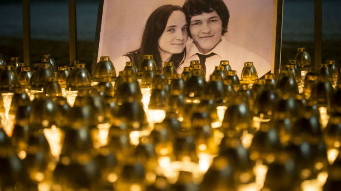 Candles and lights are placed during a protest in memory of murdered journalist Jan Kuciak and his fiancée Martina Kusnirova, seen in the photo, in Bratislava, Slovakia.