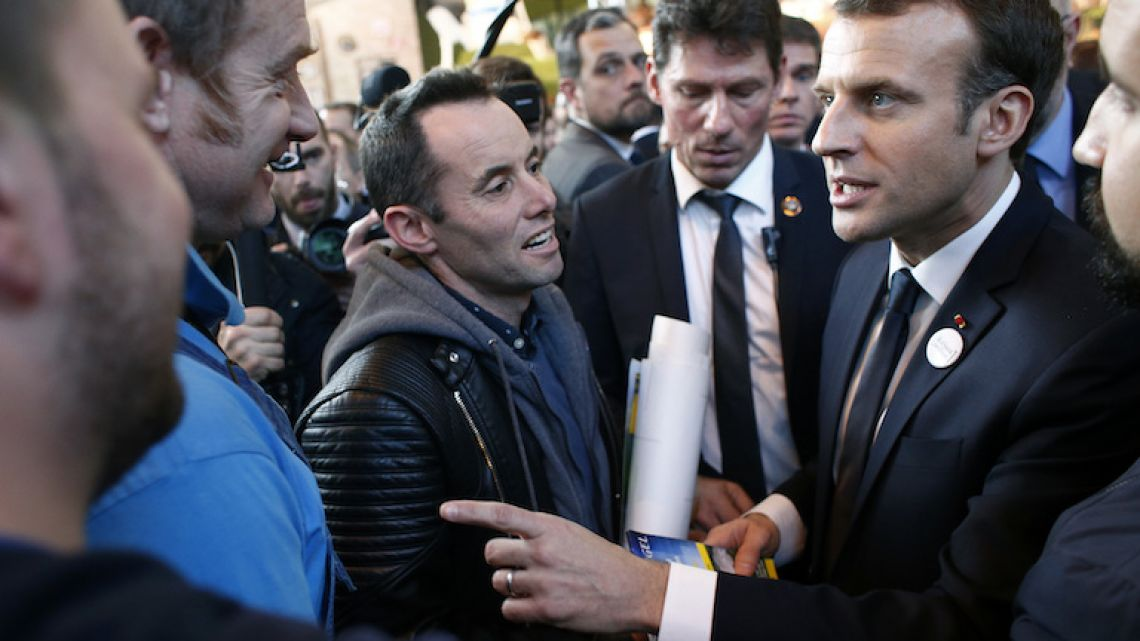 French President Emmanuel Macron, right, talks with farmers as he visits the 55th International Agriculture Fair at the Porte de Versailles exhibition center in Paris on February 24.