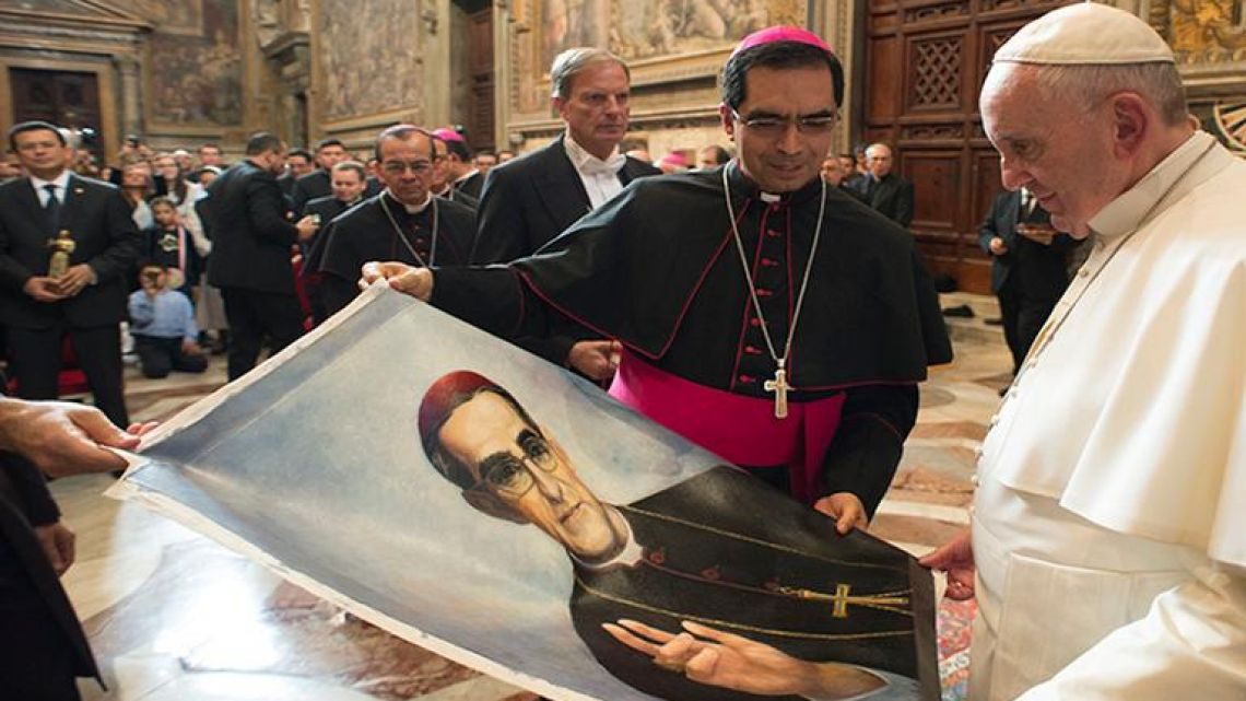 In this Oct. 30, 2015 file photo, Pope Francis is presented with an image of Roman Catholic Archbishop Oscar Romero during a private audience granted to participants to the pilgrimage from El Salvador at the Vatican.