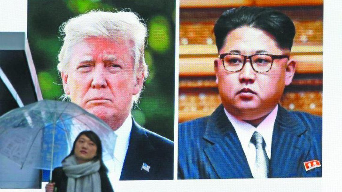 A woman walks by a huge screen in Toyko showing US President Donald Trump, left, and North Korea's leader Kim Jong-un.