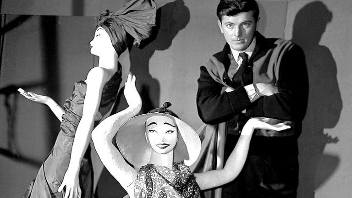In this February 1, 1952 file photo, French fashion designer Hubert de Givenchy poses with mannequins in his shop in Paris.
