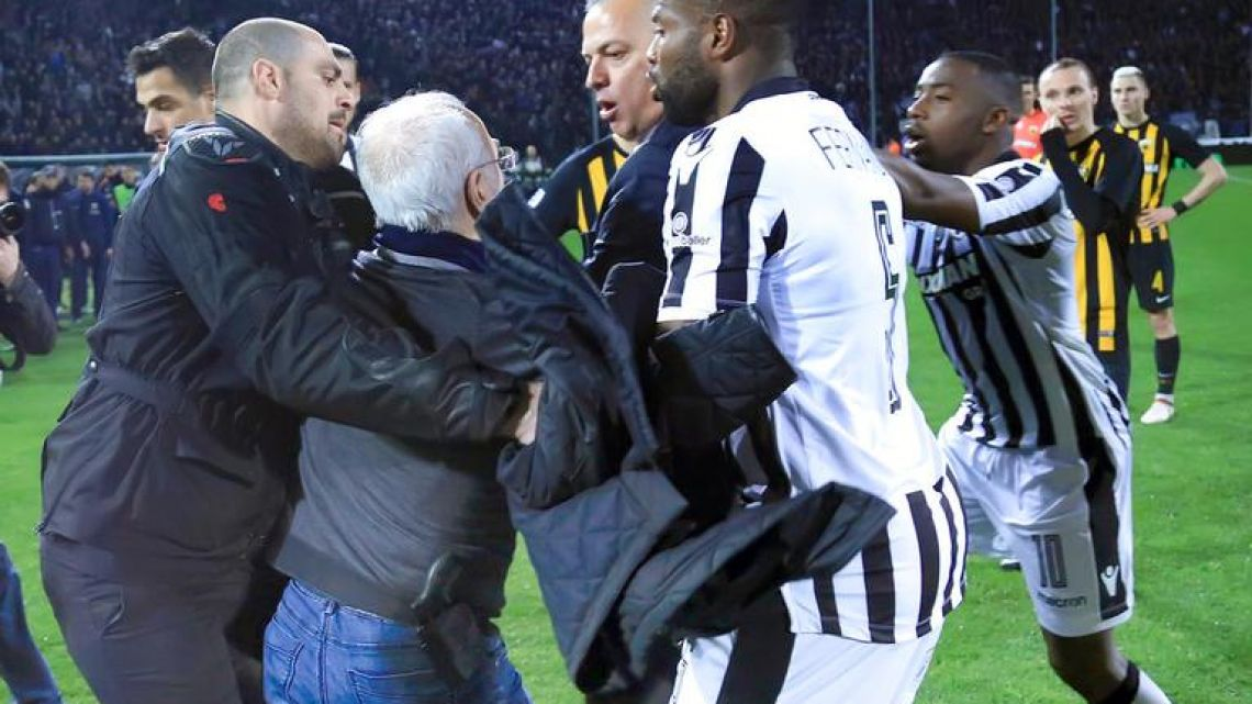 Ivan Savvidis, a Greek businessman and the owner of Greek club PAOK, approaches AEK Athens official Vassilis Dimitriadis, center, as his bodyguard and two PAOK players attempt to stop him. The incident took place during a league match between the two clubs on Sunday.