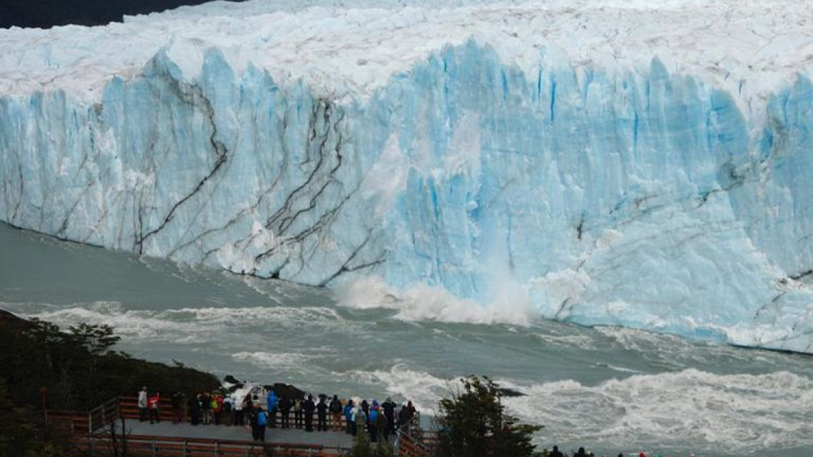 Tourists watch pieces of ice falling from the Perito Moreno glacier, at Parque Nacional Los Glaciares near El Calafate, in the province of Santa Cruz, on March 12, 2018.