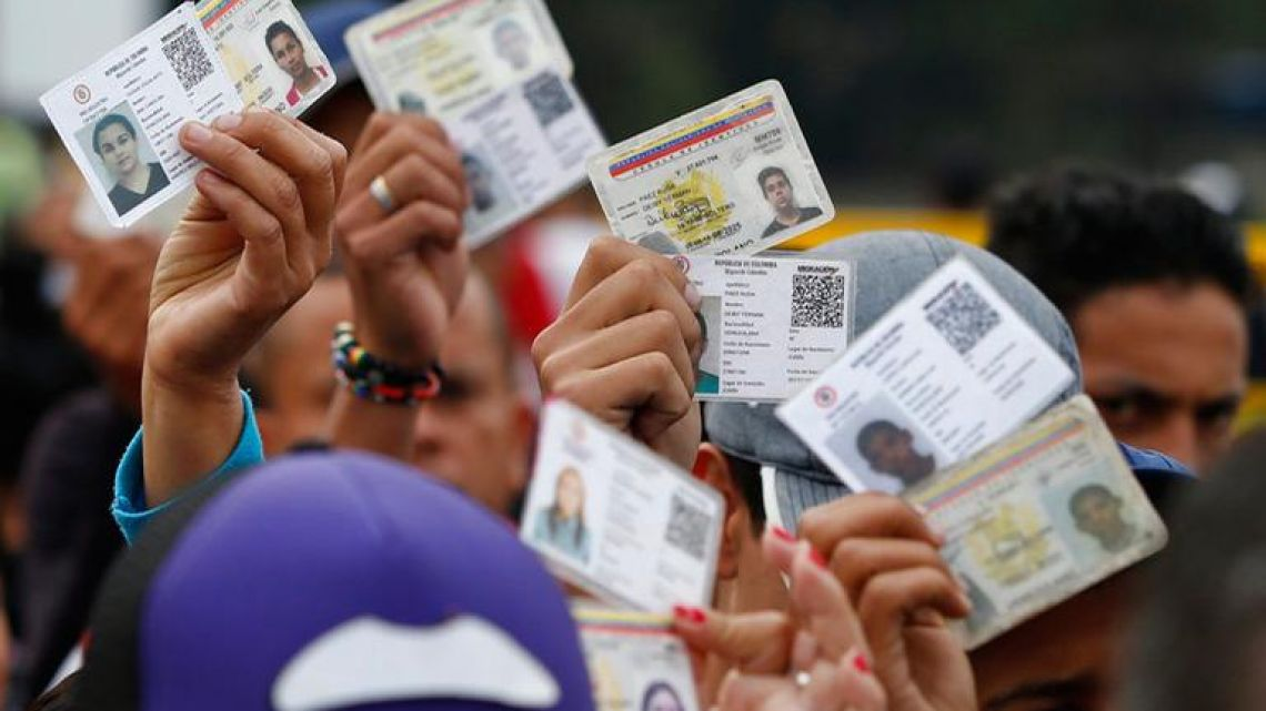 Venezuelan citizens hold up their identification cards for inspection by the Colombian immigration police, in Cucuta, Colombia, on the border with Venezuela.