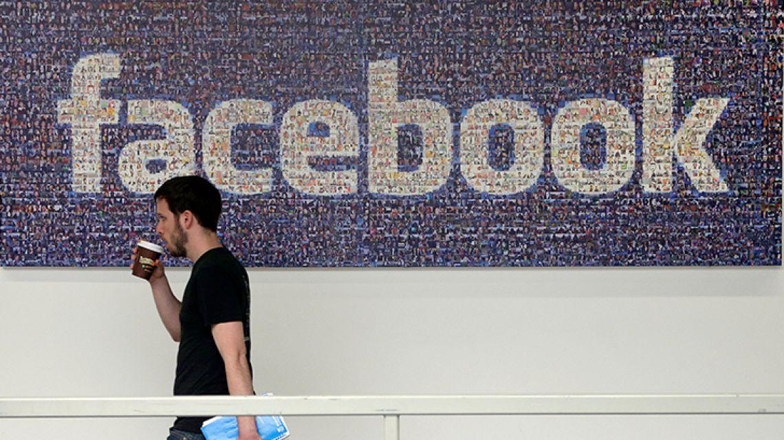 A Facebook employee walks past a sign at Facebook headquarters in Menlo Park, California.